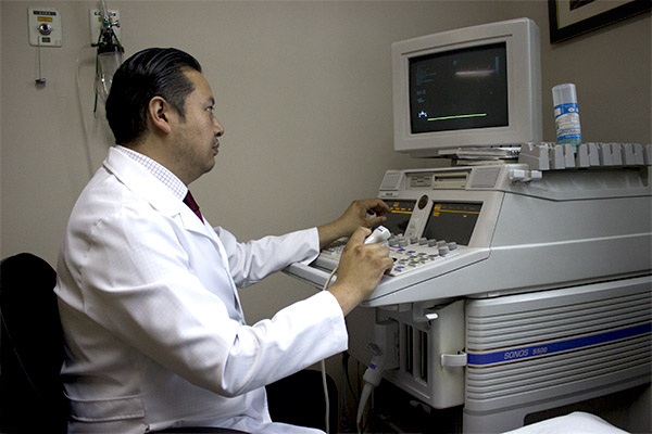 Cardiólogo Emmanuel sentado frente a una máquina para cardiología