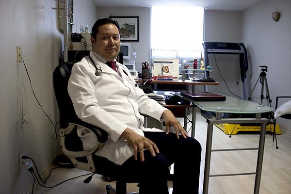 Dr. Emmanuel con bata blanca sentado frente a su escritorio